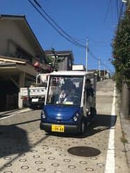 傾斜のきつい道を上り下りし、住民を運ぶ(29日、横浜市金沢区)