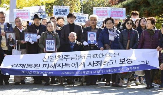 30日、判決が言い渡される前に韓国最高裁前で集会を開く原告側の支援者ら=共同