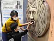 大阪大病院に設置された「真実の口」に手を入れ消毒する来院者(30日、大阪府吹田市)=共同