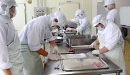 ラム肉の加工作業をする生徒たち(19日、北海道遠別町)=共同