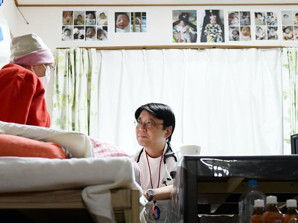 自宅で訪問診療を受けるがん患者の女性(左)。小沢院長と会話を重ねるごとに表情がほころんでいった(神奈川県内)=柏原敬樹撮影