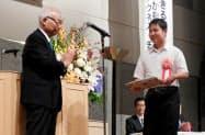 日本対がん協会の垣添忠生会長(左)から表彰されるどあらっこの中村航大さん=日本対がん協会提供