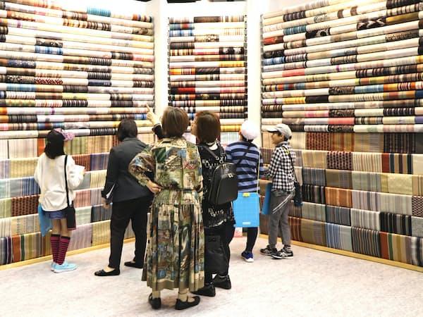 工芸エキスポで博多織の生地を777枚吊した展示に見入る来場者(2日、福岡市博多区)