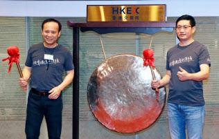 9月28日、香港取引所上場の記念式典でドラを鳴らす衆安在線財産保険の歐亜平会長(左)