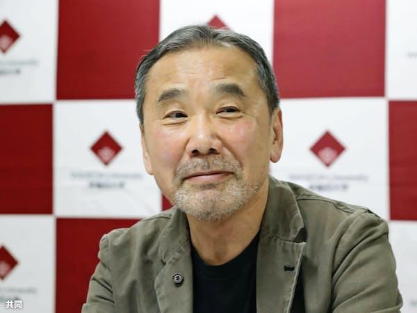 早大に寄贈する書籍にサインし、写真に納まる作家の村上春樹さん=4日午後、東京都新宿区