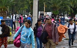 4日、メキシコシティで、同市当局が用意した収容施設に入ろうとする移民集団