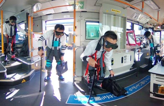 専用器具をつけ高齢者を疑似体験する近鉄バスの運転手たち(大阪府摂津市)=超広角レンズ使用
