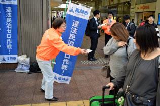 福岡市や福岡県警は違法民泊の情報提供を呼びかけたチラシの入ったティッシュを配布した(6日、福岡市中央区)