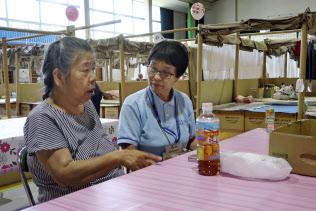 避難所で井上加代子さん(左)の話を聞く傾聴ボランティアの草加昭子さん(岡山県倉敷市真備町地区)=共同