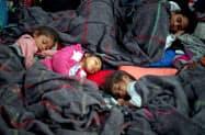 収容場所で休む移民集団の子どもたち(7日、メキシコシティ)=ロイター