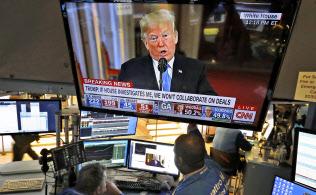 ニューヨーク証券取引所のモニターで放映されるトランプ大統領の記者会見(7日)=AP