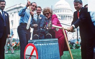 1987年7月、米議会前で東芝製ラジカセをハンマーでたたき壊す米議員ら=AP