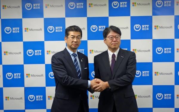 記者会見後に握手を交わすNTT西日本の小林充佳社長(左)と日本マイクロソフトの佐藤知成常務執行役員(8日、大阪市)