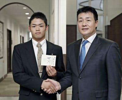 指名あいさつに訪れた中日の与田監督(右)と握手する根尾=共同