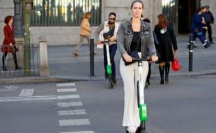 スペインでも電動スクーターが日常生活に入り込んでいる。女性が乗るのは米ライム社製=ロイター