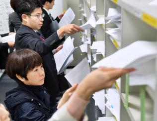 決算発表の資料を棚に入れる企業の担当者ら(9日、東証)