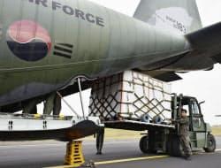 11日、北朝鮮に送るミカンを輸送機に積む韓国軍関係者(韓国・済州)=韓国国防省提供・共同