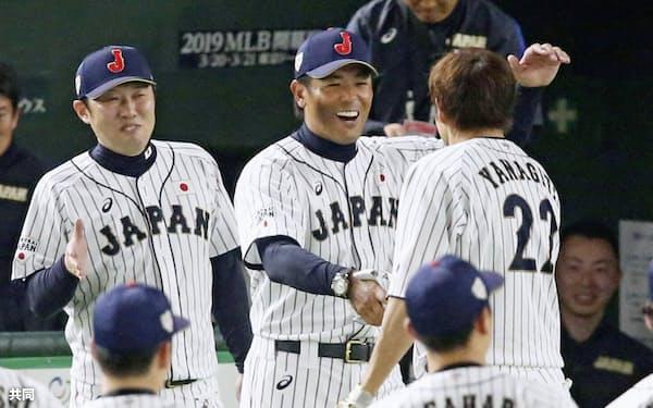 日米野球第1戦で逆転サヨナラ2ランを放った柳田(右奥)を迎える稲葉監督(中央奥)=共同