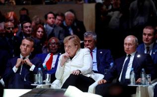 11日、パリ平和フォーラムに出席した(手前左から)マクロン氏、メルケル氏、プーチン氏=ロイター