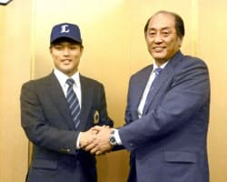 入団に合意し、渡辺久信SD(右)と握手する西武ドラフト1位の松本航投手(13日午後、東京都内のホテル)=共同