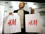従来のプラスチック製バッグ(左)と12月から使用する有料の紙製バッグを持つH&M日本法人のルーカス・セイファート社長(13日午前、東京都渋谷区)