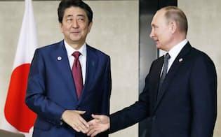 会談前にロシアのプーチン大統領(右)と握手する安倍首相(14日、シンガポール)=共同