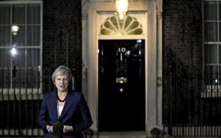 14日夜、英首相官邸前で声明を読み上げるメイ首相=AP