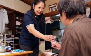 介護サービスの利用者(右)に水が入ったコップと薬を手渡す介護士(横浜市)