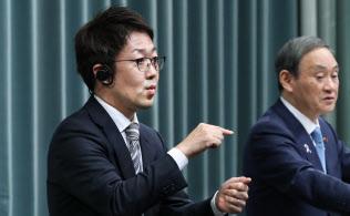 記者会見で菅義偉官房長官(右)の発言を手話通訳する(首相官邸)