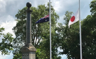 慰霊碑の奥で日豪の国旗が揺れています