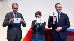 地方集会で演説順を示すカードを掲げるメルツ氏(左)、クランプカレンバウアー氏(中)、シュパーン氏=ロイター