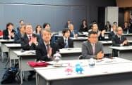 重さの単位「キログラム」などの定義変更が決まり、産業技術総合研究所の研究者が拍手した(16日、茨城県つくば市)
