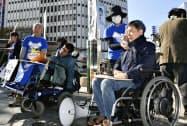 木造復元する名古屋城天守閣へのエレベーター設置を求め、署名活動する障害者団体のメンバーら(17日午後、名古屋市)=共同