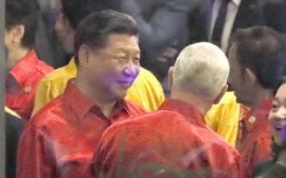 17日、APECの夕食会会場でペンス米副大統領(手前右端、背中の人物)と立ち話をする中国の習近平国家主席。左端は安倍首相(パプアニューギニアのポートモレスビー)=共同