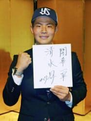ヤクルトに入団が決まり、笑顔でポーズをとる国学院大の清水昇投手(18日、東京都内のホテル)=共同
