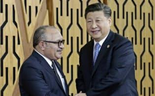 パプアニューギニアのオニール首相(左)と握手する中国の習近平国家主席=AP