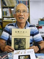 被爆者証言集の創刊号「長崎の証言」を手にする事務局長の森口さん(7月、長崎市)=共同