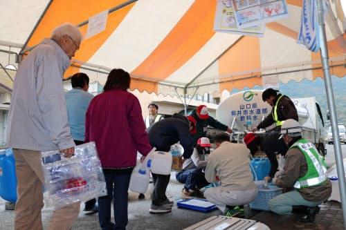 町職員らによる給水を待つ住民(19日、山口県周防大島町)
