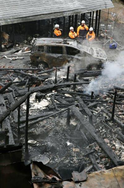 火災で全焼した建物と焼け焦げた車(22日午前7時、福島県小野町)=共同