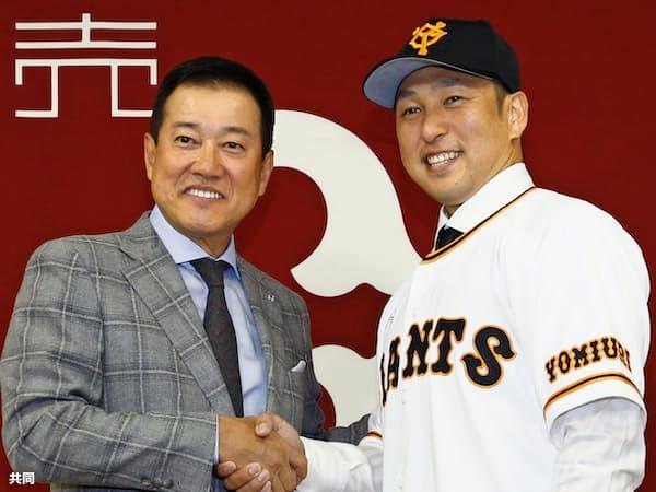 巨人の入団記者会見で、原辰徳監督(左)と握手する中島宏之内野手(22日、東京ドーム)=共同