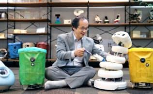「弱いロボット」と並んで座る豊橋技術科学大の岡田美智男教授=上間孝司撮影