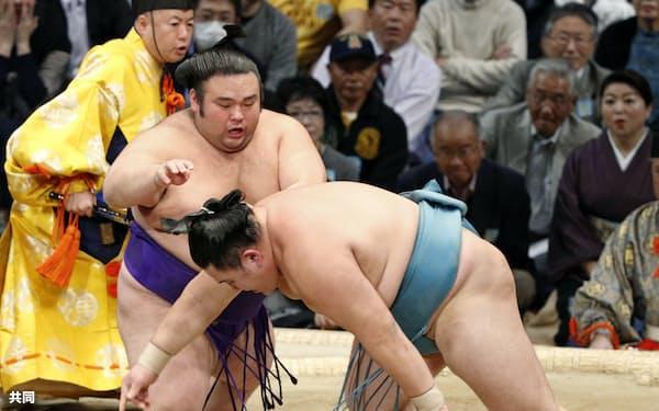 貴景勝(左)が突き落としで玉鷲を下す(22日、福岡国際センター)=共同