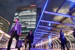 臨時取締役会が行われている日産自動車の本社前を行き交う人たち(22日夜、横浜市西区)