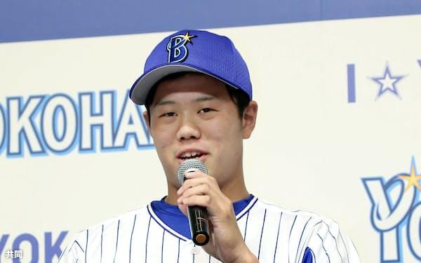 DeNAの新入団記者会見で抱負を語る上茶谷大河投手。右はラミレス監督(22日、横浜市内のホテル)=共同