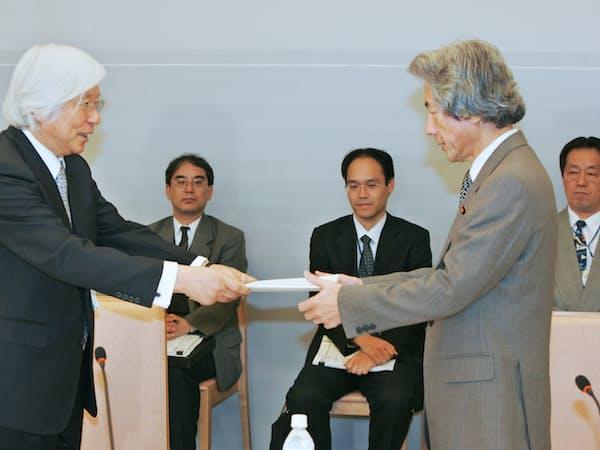 皇室典範に関する有識者会議で、小泉首相(右)に報告書を手渡す吉川座長(左)(2005年11月、首相官邸)