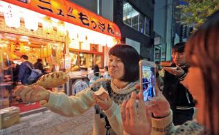 立ち飲み居酒屋「ニューもっさん」。店の前で、名物のチーズハットグを食べている場面を撮影する若者が目立つ(水戸市)
