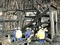 7人の遺体が見つかった福島県小野町の火災現場を調べる消防隊員ら(23日午前)=共同