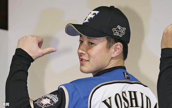 新入団選手発表で背番号「18」を披露する日本ハムの吉田輝星投手(23日、札幌市内のホテル)=共同