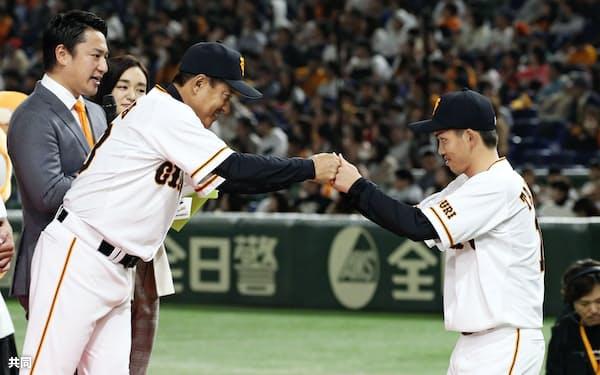 新入団選手発表で原監督(左)とグータッチする高橋優貴投手(23日、東京ドーム)=共同