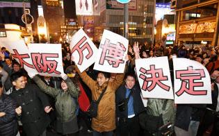 2025年の万博開催国に大阪が決まり、喜ぶ人たち(24日未明、大阪市中央区)